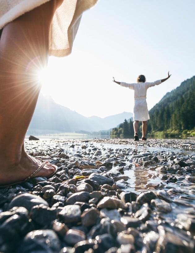 Paar im Bademantel am Kieselstrand: Perfekter Wellnessurlaub für zwei im Best Alpine Wellnesshotel Nesslerhof in Großarl