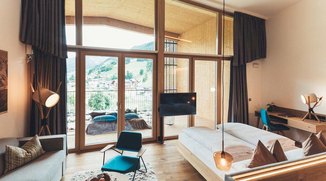 Modernes Doppelzimmer mit großer Glasfront, Balkon und Liegemöglichkeit im 4*S Wellnesshotel Nesslerhof in Großarl, Salzburger Land