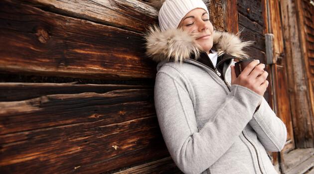 Frau mit Winterjacke und weißer Mütze und Teetasse vor einer Almhütte - perfekter Winterurlaub mit Wellness im 4*S Best Alpine Wellness Hotel Nesslerhof, Großarl