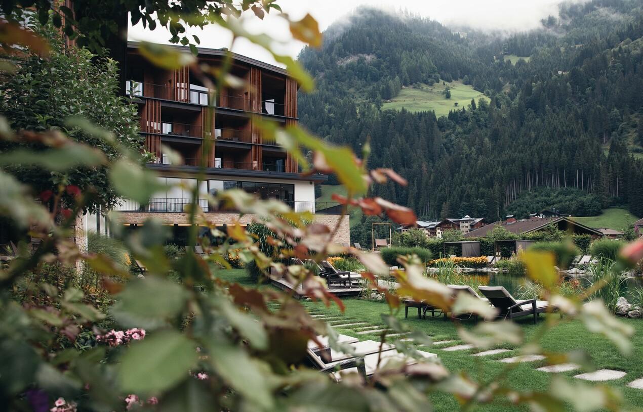 Blick durch Sträucher auf den Hotelgarten mit Naturbadeteich und Sonnenliegen im 4*S Wellnesshotel Nesslerhof in Großarl, Salzburger Land.