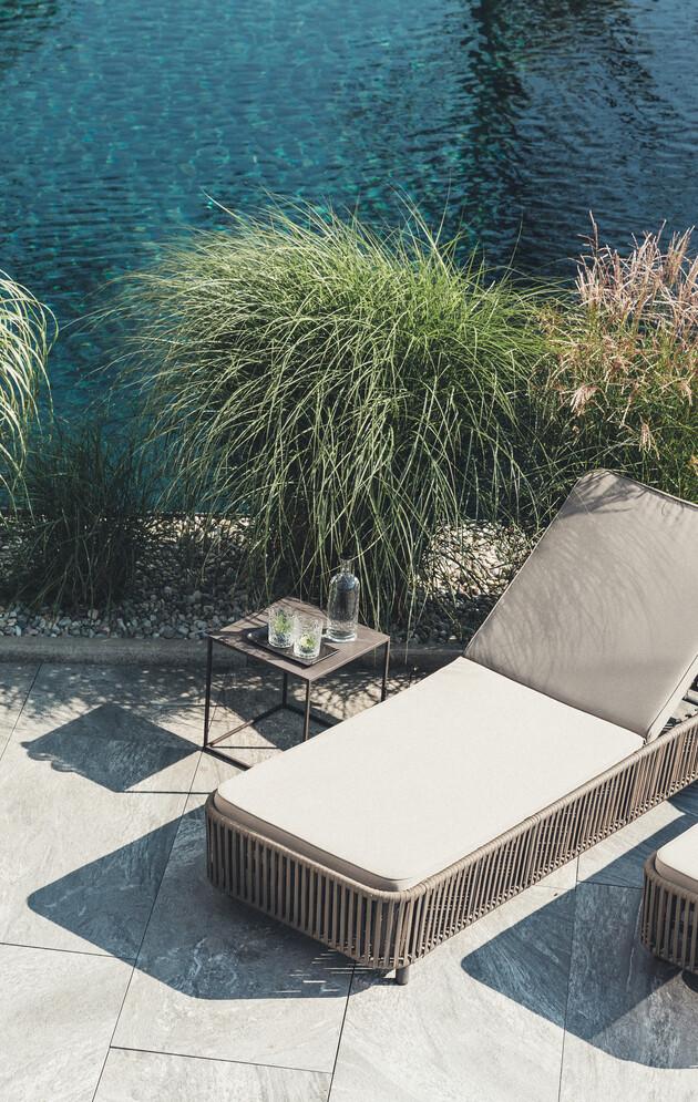 Gemütliche Sonnenliege am Naturbadeteich im 4*S Wellnesshotel Nesslerhof in Großarl, Salzburger Land.