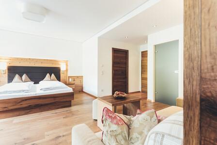 Großzügiges Doppelbett in der lichtdurchfluteten Suite mit Holzfußboden im 4*S Hotel Nesslerhof, Großarl