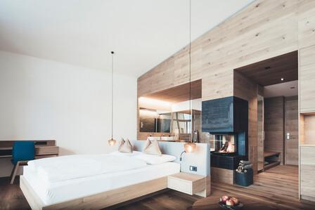 Großzügiges Doppelbett mit Hängeleuchten und Kamin in der modernen Suite Weitblick im Hotel Nesslerhof, Großarl