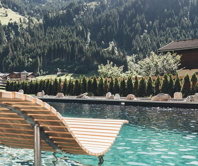 Im Wasser schwebende Liege aus Holz mit Blick auf die Berge im 4*S Wellnesshotel Nesslerhof in Großarl, Salzburger Land