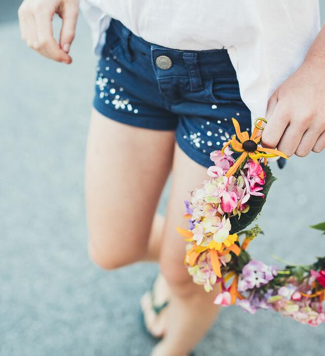 Mädchen hält einen Blumenkranz beim Urlaub im Familienhotel Nesslerhof in Salzburg
