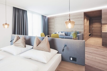 Suite Freiraum mit großzügigem Doppelbett, Couch und Panoramafenstern im Hotel Nesslerhof, Großarl