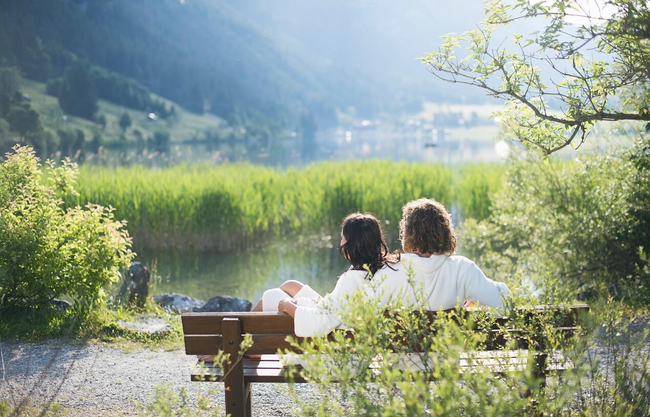 Paar im Bademantel auf Holzbank am Seeufer - Urlaub im Hotel Nesslerhof, Großarl